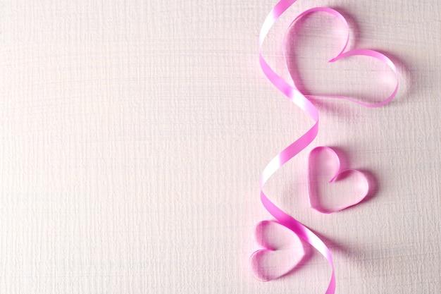 Nastro a forma di cuore su fondo in legno colorato