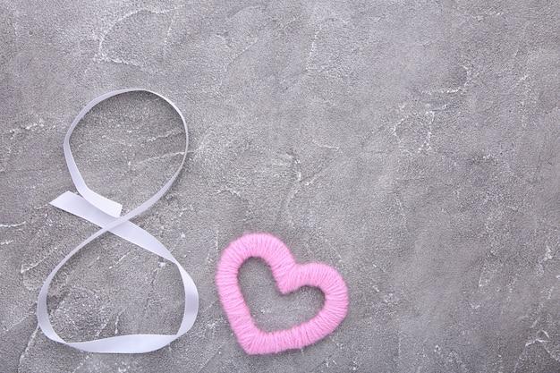 Nastri a forma di 8 marzo con cuore su grigio. giornata internazionale della donna