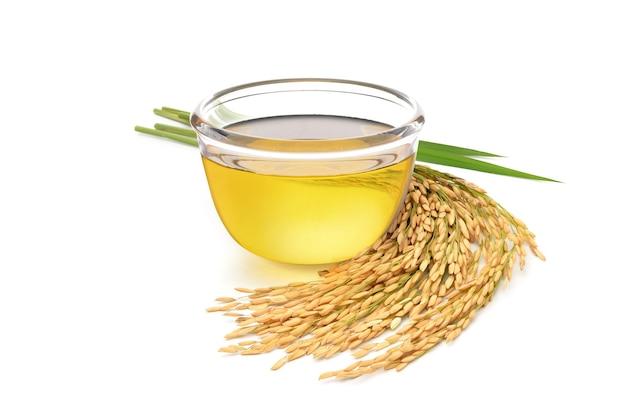Olio di crusca di riso con orecchie di riso e foglie isolati su sfondo bianco.