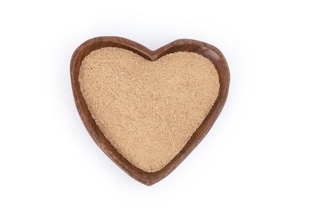 Crusca di riso posta a forma di cuore in legno posto isolato su bianco. vista dall'alto.
