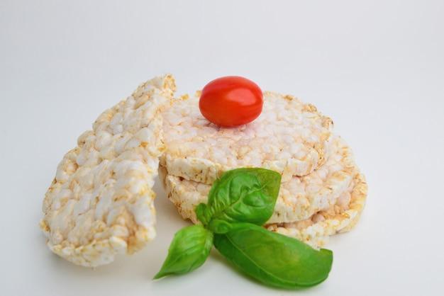Torta di riso (cialde) con pomodorini e foglia di basilico verde su sfondo bianco. uno spuntino sano e vegetariano. cibo semplice.