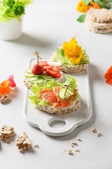 Torta di riso croccante con pesce rosso e verdure su sfondo bianco.
