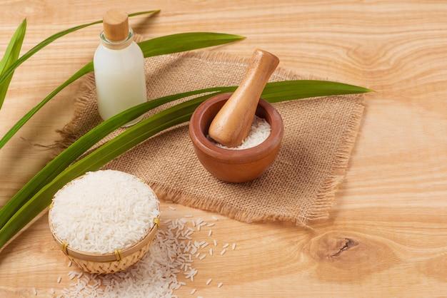 Farina di riso in una ciotola di legno, latte e riso sui vecchi precedenti di legno