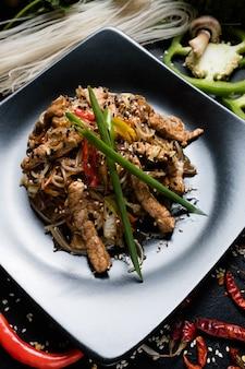 Tagliatelle di riso maiale e verdure su un piatto