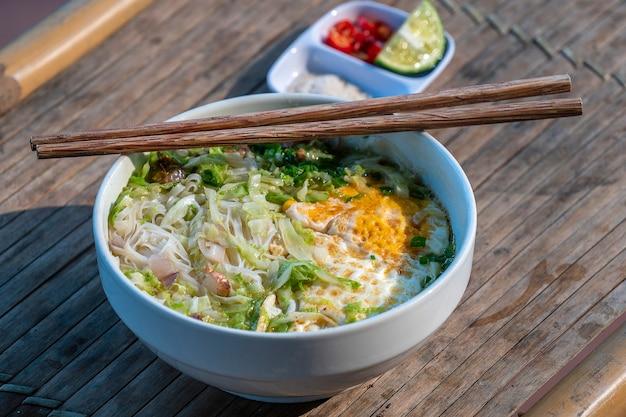 Zuppa di spaghetti di riso con tanti ingredienti deliziosi. zuppa tradizionale vietnamita, primo piano