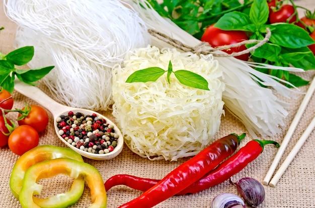 Gli spaghetti di riso sono diversi, pomodori, peperoni, bacchette, aglio, basilico su uno sfondo di tela di sacco