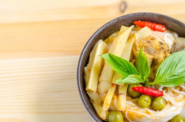 Tagliatelle di riso in salsa di curry di pollo con verdure su fondo di legno