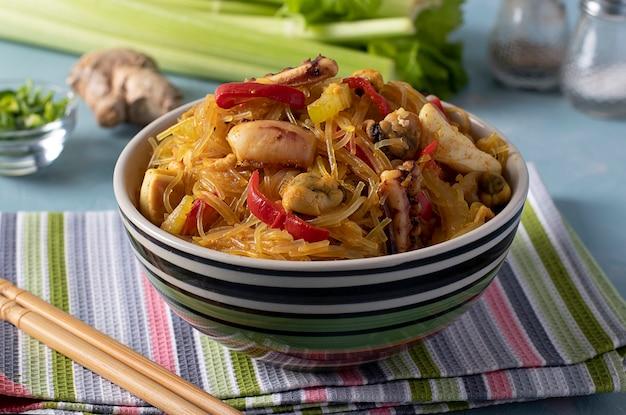Spaghetti di riso funchoza con frutti di mare. pasta al cellophane, cozze, calamari e polpi, spuntino sano per un pasto asiatico in una ciotola su uno sfondo azzurro. avvicinamento