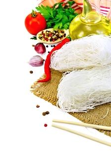Tagliatelle di riso sottili, pomodori, peperoni diversi, bacchette, aglio, prezzemolo, olio, sacchi isolati su sfondo bianco