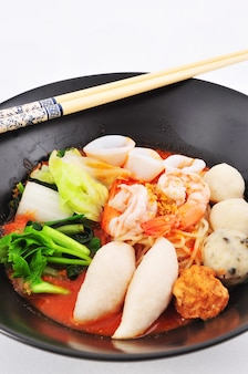 Spaghetti di riso con gamberi e polpetta di pesce in zuppa rossa yen ta fo