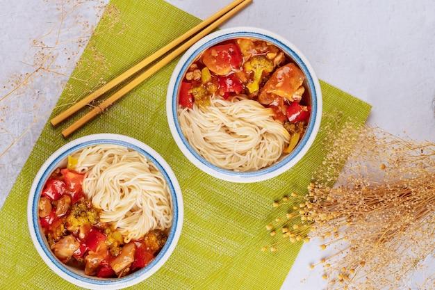 Spaghetti di riso con verdure saltate in padella nella ciotola