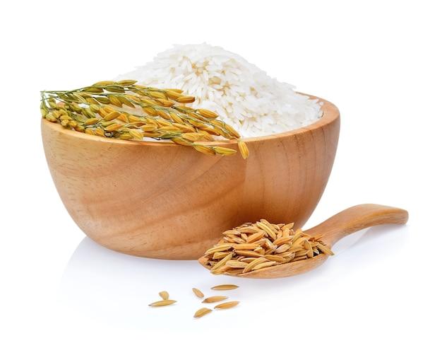 Piante di riso, chicchi di riso al gelsomino tailandese in una ciotola di legno su sfondo bianco