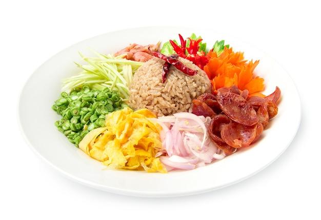 Riso condito con pasta di gamberi o mix di riso fetta di cipolla rossa, fagioli, mango, uovo fritto, fusione di stile di cibo tailandese decorare con vista laterale di verdure intagliate isolato su sfondo bianco