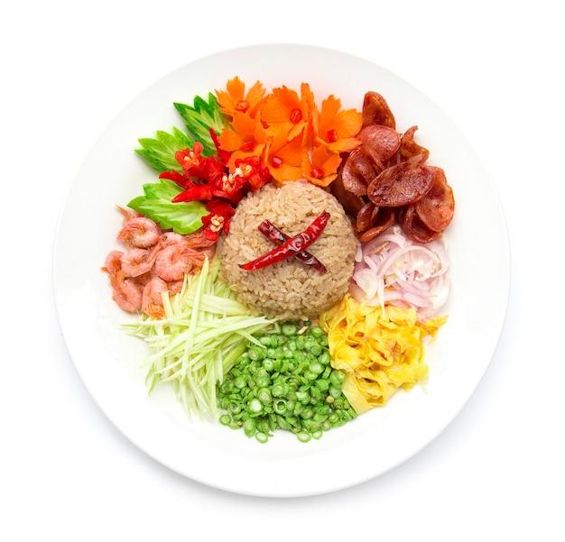 Riso condito con pasta di gamberi o mix di riso fetta di cipolla rossa, fagioli, mango, uovo fritto, fusione di stile di cibo tailandese decorare con vista dall'alto di verdure intagliate isolato su sfondo bianco