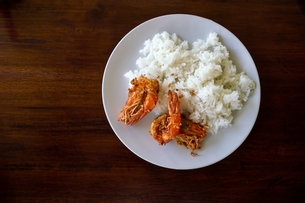 Aglio fritto del gamberetto e del riso in un piatto bianco
