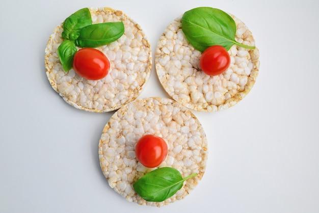 Spuntino di riso con pomodorini, basilico su sfondo bianco. spuntino dietetico. vista dall'alto. nutrizione appropriata.