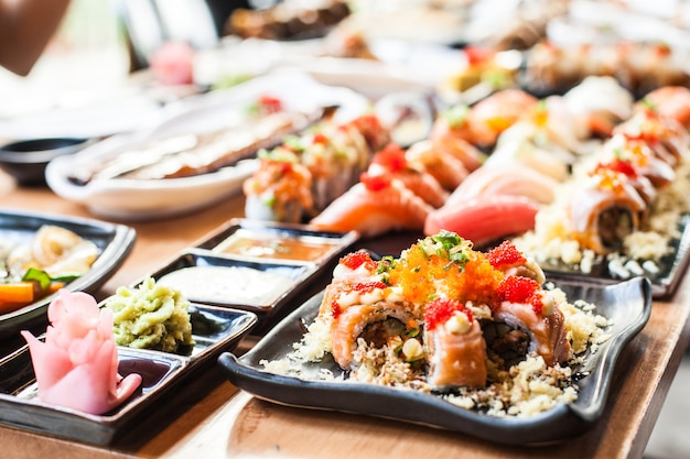 Riso sushi con maki set cibo giapponese su piastra nera nel ristorante