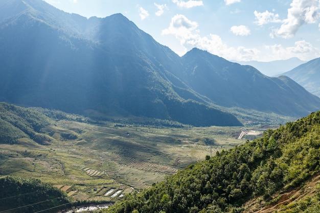 Terrazze di riso sul fianco della montagna sotto i raggi del sole raggi di sole sulle colline