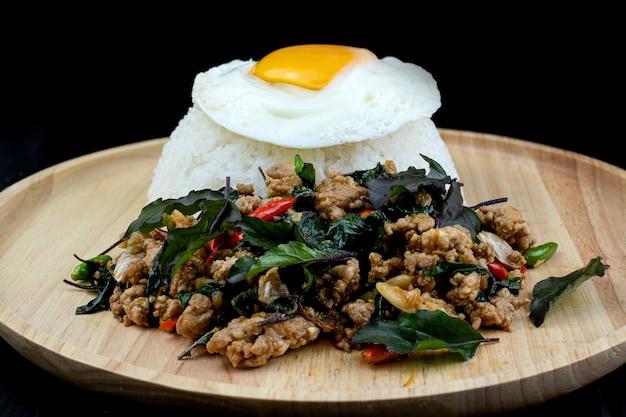 Maiale fritto piccante ricoperto di riso con foglie di basilico guarnite con uova fritte su piatto di legno