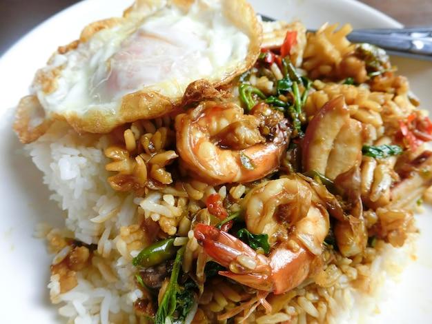 Riso condito con gamberi al basilico saltati in padella, calamari e uovo fritto in un piatto bianco