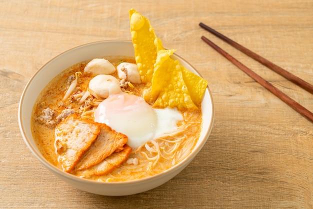 Vermicelli di riso con polpette, maiale arrosto e uova in zuppa piccante - tom yum noodles