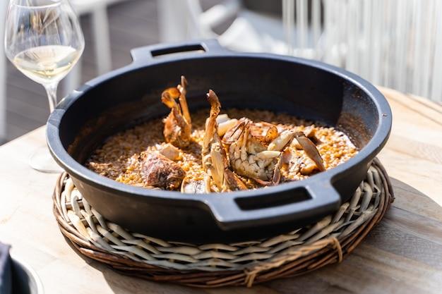 Riso ai frutti di mare servito in una pentola di ferro in un tavolo di legno con un bicchiere di vino