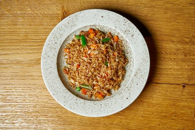 Riso con le verdure su un piatto bianco su una tavola di legno. cibo vegetariano. nutrizione dietetica e sana. vista dall'alto