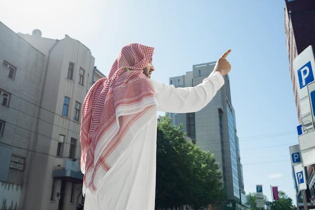 Ritratto di un ricco uomo arabo durante l'acquisto di immobili, centro affari in città. etnia, cultura, inclusione. fiducioso uomo d'affari in abbigliamento tradizionale che fa un affare di successo. finanza, economia.