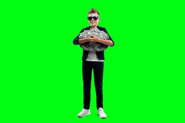 Un ragazzo ricco con gli occhiali tiene in mano dollari sullo sfondo di banconote che cadono, sa come fare soldi. sfondo verde. pioggia di denaro, educazione finanziaria, giovane milionario, investimento, guadagno.