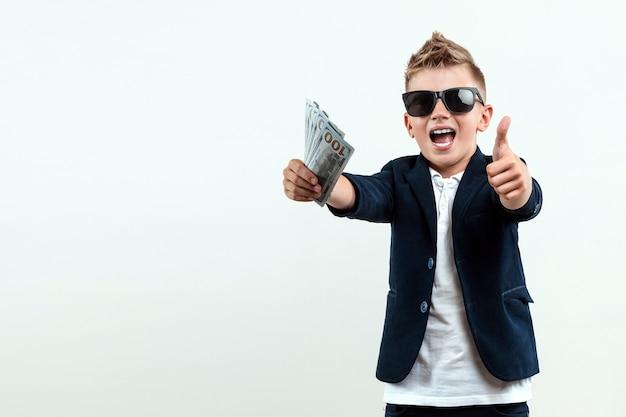 Un ragazzo ricco con gli occhiali tiene i dollari sullo sfondo delle banconote che cadono. sa come fare soldi. pioggia di soldi, educazione finanziaria, giovane milionario, investimenti, prestiti, vincite.