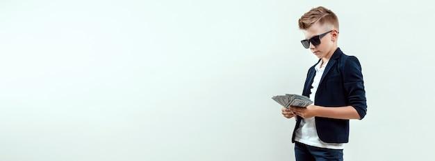 Un ragazzo ricco su uno sfondo chiaro tiene in mano un pacco di dollari. educazione finanziaria.