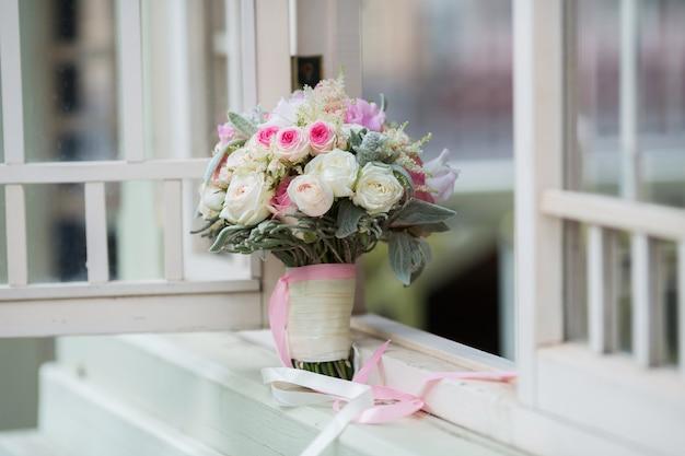 Ricco mazzo di peonie rosa e fiori di rose lilla eustoma foglia verde nella finestra