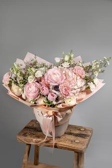 Ricco mazzo di fiori rosa e rossi e lilla. eustoma rose fiori sbocciano, foglia verde in vaso di vetro. profumo fresco di primavera. sfondo estivo