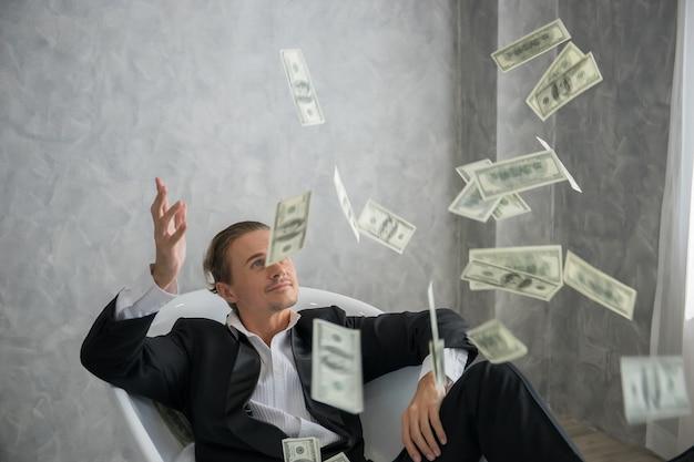 L'uomo d'affari ricco che si trova in vasca riempita di banconote del dollaro. concetto di business di successo.