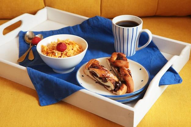 Ricca colazione continentale su una tavoletta di legno bianca e un divano giallo. cornetti croccanti francesi, muesli, frutti di bosco dolci e caffè caldo per gustosi pasti mattutini. delizioso inizio di giornata.