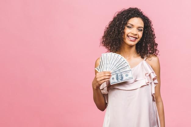 Ragazza ricca! vincitore di soldi! bella donna afroamericana sorpresa in vestito che tiene i soldi e guardando la telecamera isolata su sfondo rosa.