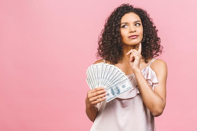 Ragazza ricca! vincitore di soldi! pensando bella donna afroamericana in vestito che tiene soldi isolati su sfondo rosa.