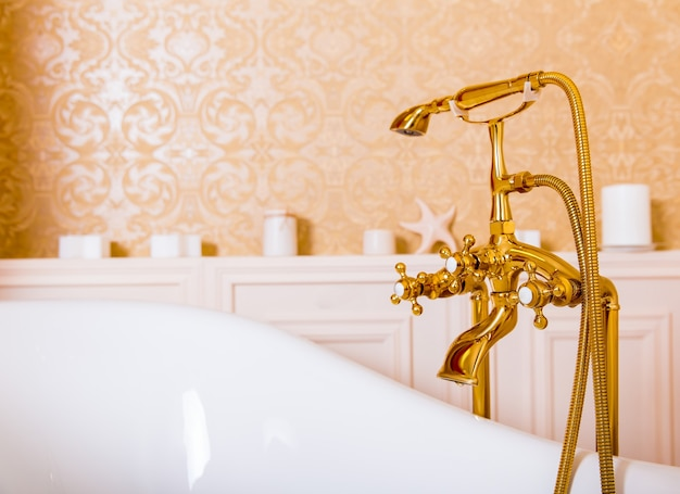 Ricco rubinetto d'oro e bagno bianco in bagno. attrezzature sanitarie di lusso
