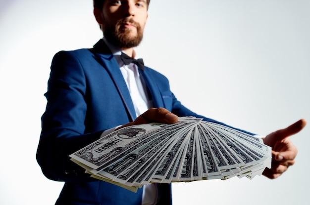 Ragazzo ricco con una pila di banconote denaro vestito classico gesticolando con le mani.