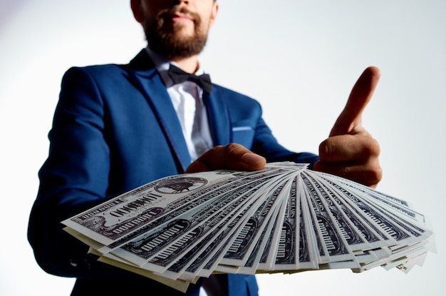 Ragazzo ricco con una pila di banconote denaro vestito classico gesticolando con le mani