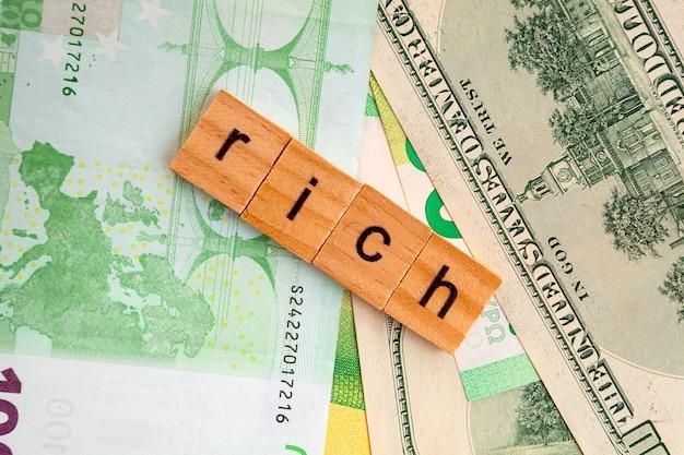 Ricca iscrizione su cubi di legno sulla trama di dollari americani e banconote in euro