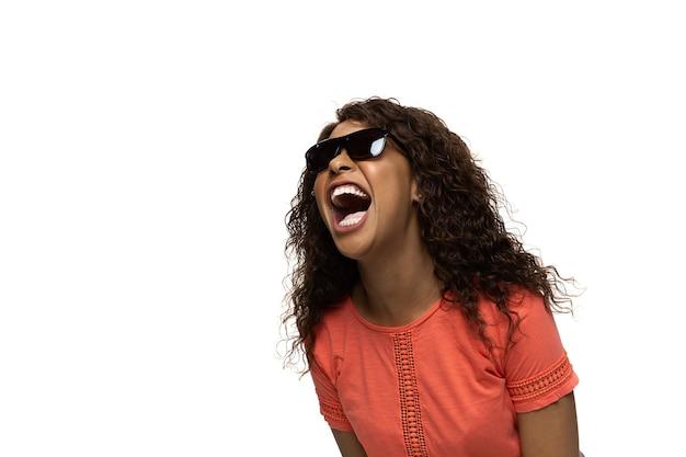 Risate ricche. giovane donna afro-americana con emozioni e gesti popolari divertenti e insoliti su sfondo bianco studio. emozioni umane, espressione facciale, vendite, concetto di annuncio. look alla moda ispirato a