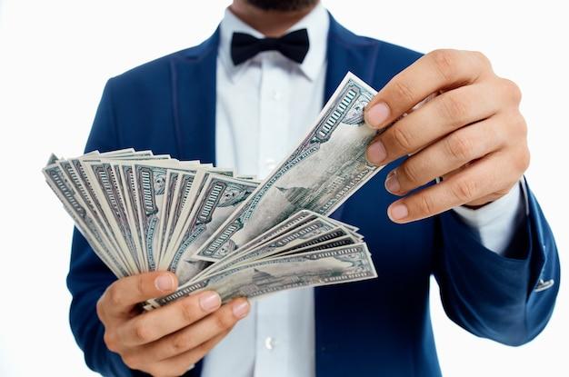 Uomo ricco in giacca e camicia blu con una mazzetta di soldi in mano.