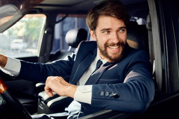 Uomo ricco in tuta che guida un viaggio in macchina