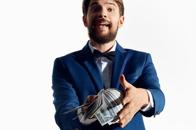 Uomo ricco con un pacco di soldi in mano e un abito classico su un bianco.