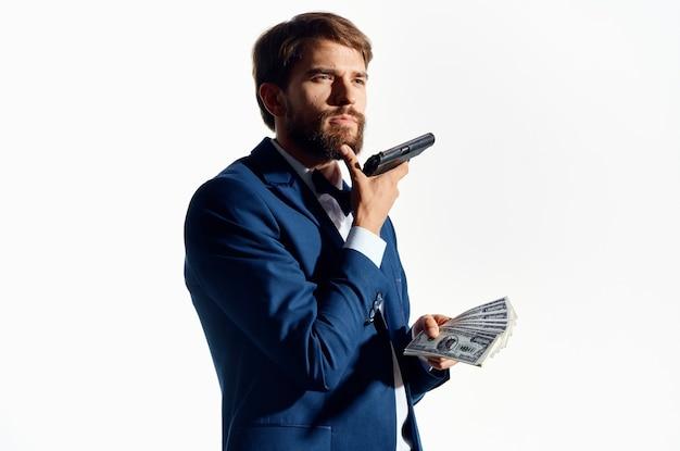 Uomo ricco con pistola e batuffolo di denaro vestito classico sfondo bianco.