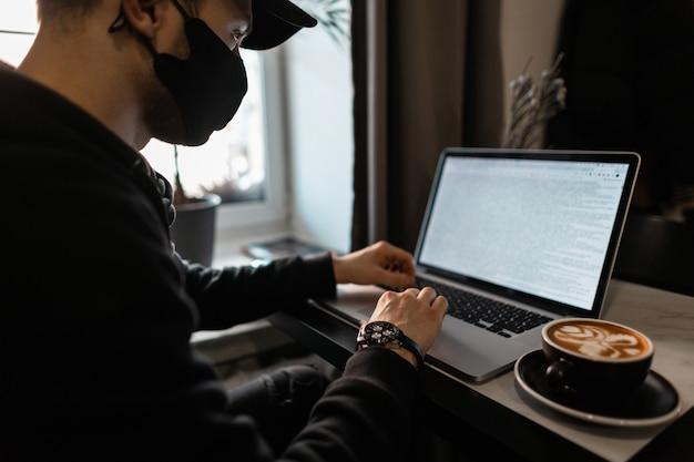 Un ricco professionista in abiti neri con una maschera protettiva nera e un berretto è seduto in un bar, lavora al suo laptop e beve caffè.