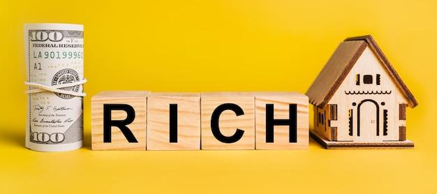 Ricco con modello in miniatura di casa e soldi su una parete gialla