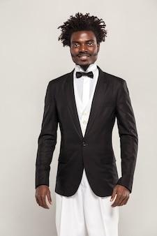 Gentleman riccamente africano con stile di capelli afro in smoking in stile classico e farfallino sorridente. studio al coperto e isolato su sfondo grigio