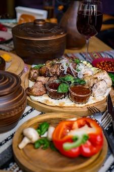 I piatti riccamente apparecchiati della cucina georgiana, un sacco di cibo delizioso, vino, frutta e carne arrosto